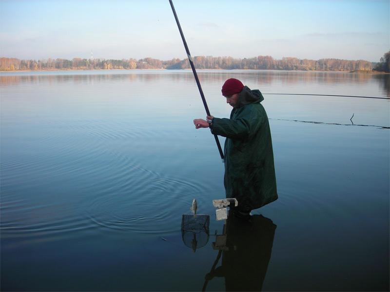 Рыбак поколена в воде