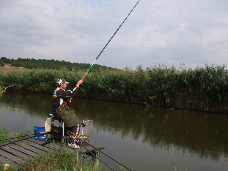 Рыбак с удочкой на пристанет