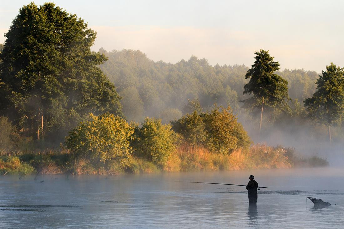 Рыбак в воде в тумане