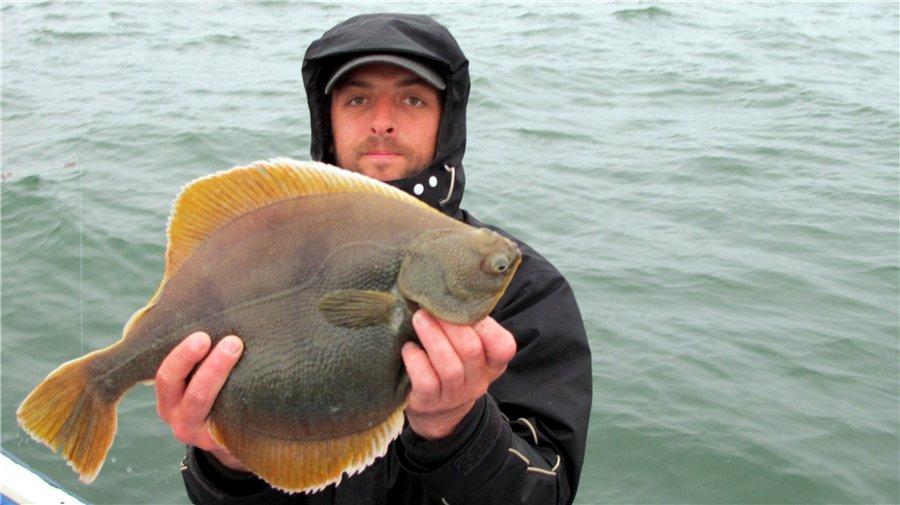 Рыбак с камбалой в руках