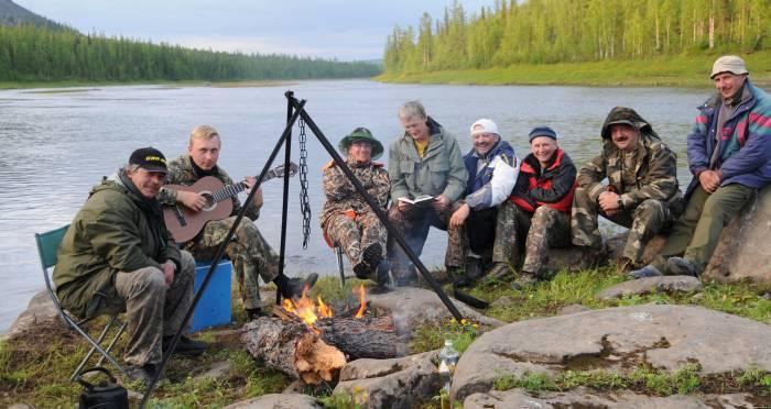 Группа рыбаков у костра с гитарой