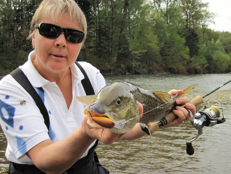 Женщина рыбак с удочкой и рыбой