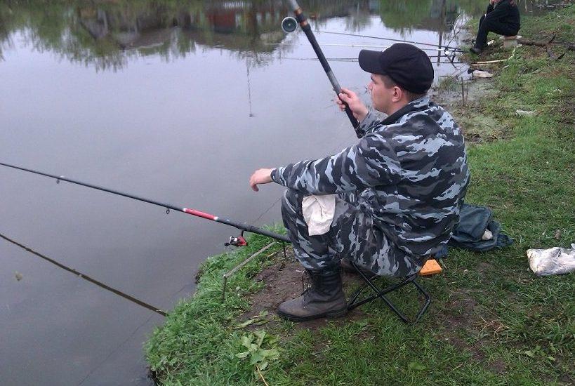 Рыбак с удочками у озера