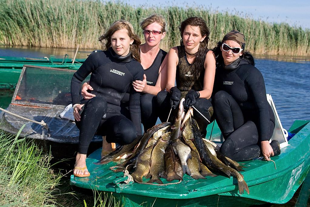Девушки охотницы с рыбой в лодке