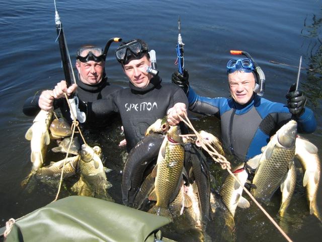 Трое мужчин в воде с рыбой