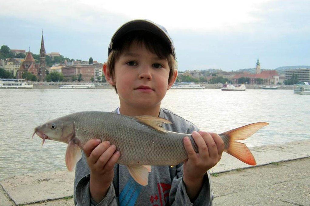 Юный рыбак с усачом в руках