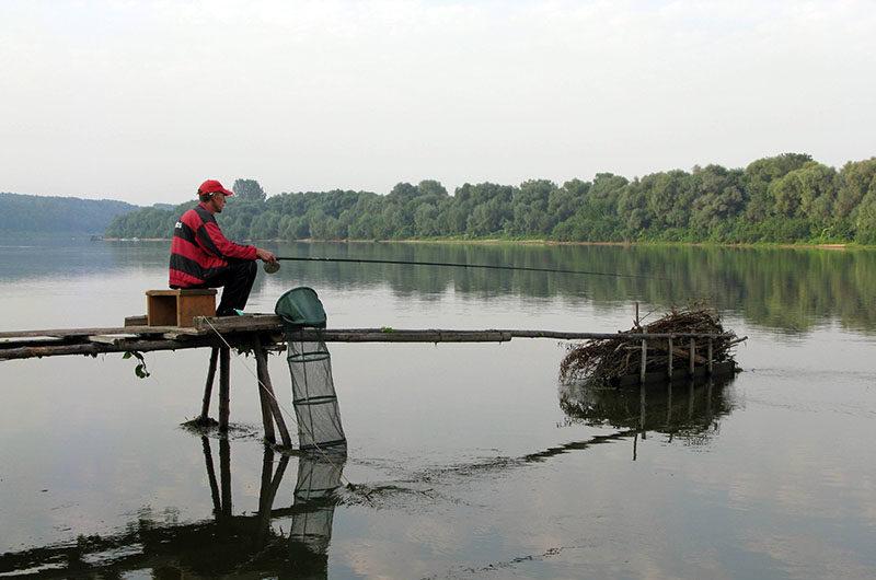 Рыбак на пристани с удочкой