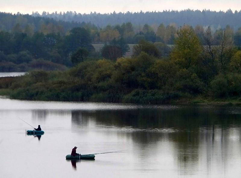 Два рыбака в лодках на фоне озера в Белоруссии