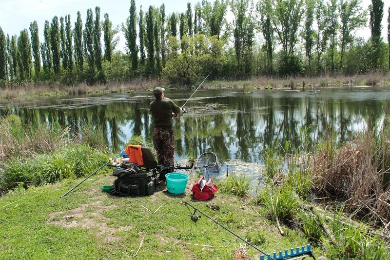 Рыбак с удочкой у озера