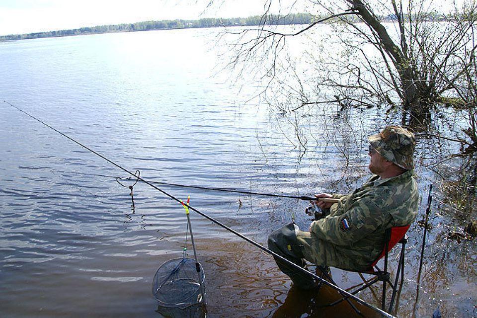 Рыбаку на берегу озера с удочками