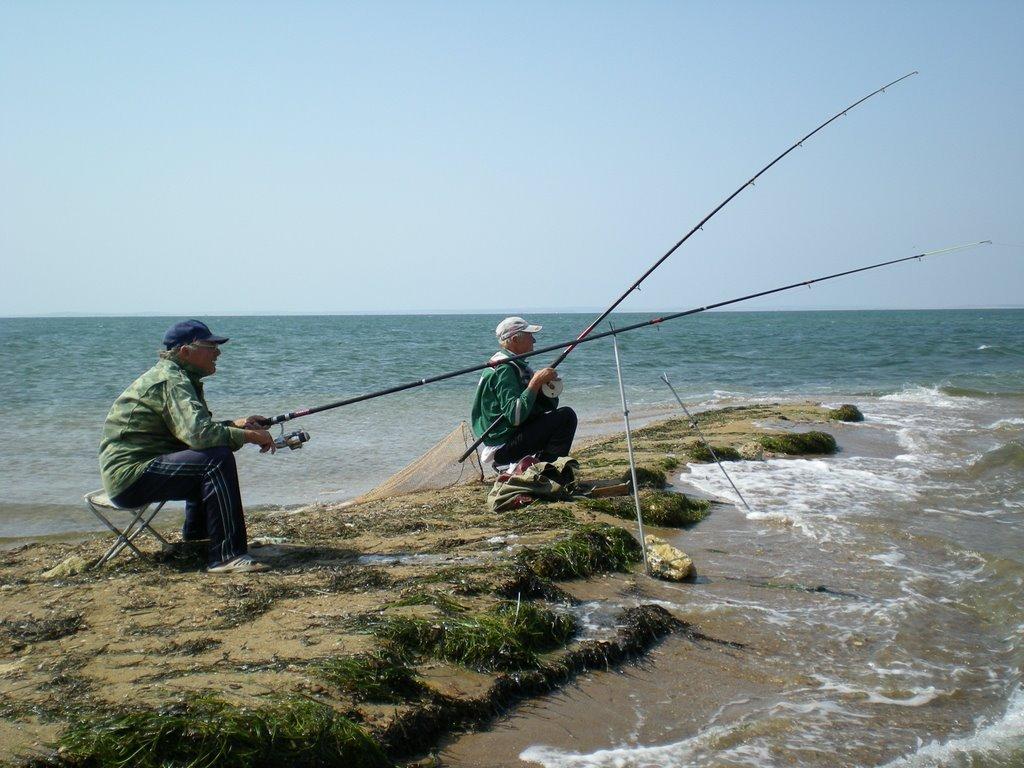 Два рыбака с удочками на камне