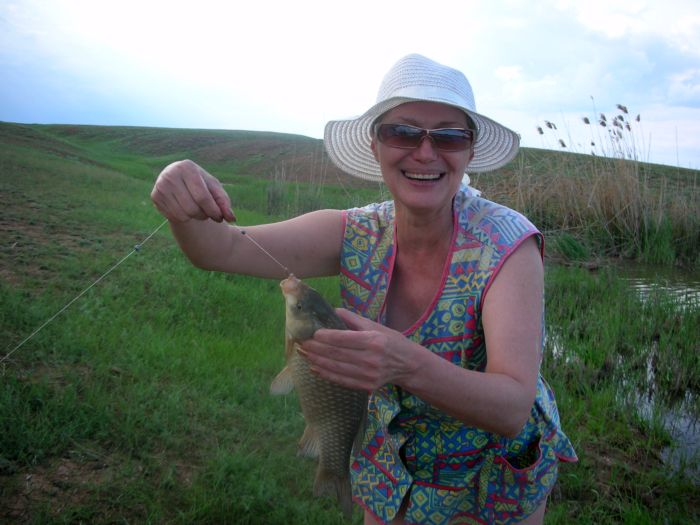 Женщина в шляпе с крупным карпом