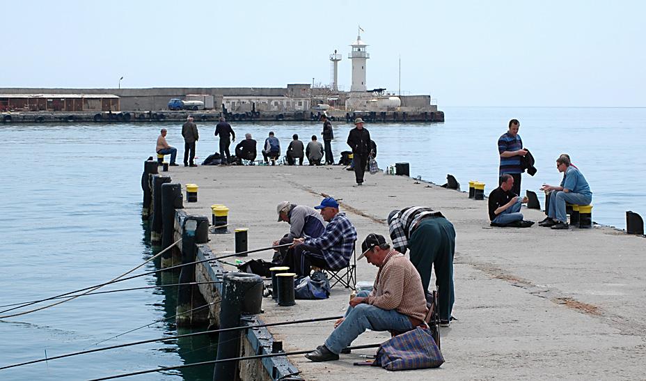 Толпа рыбаков на пирсе