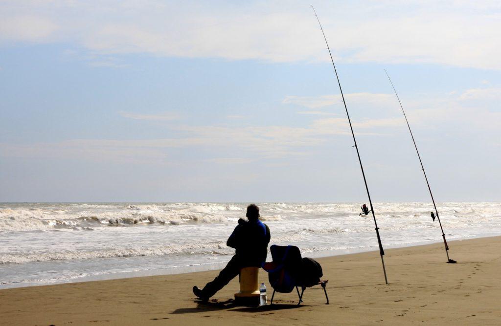 Одинокий рыбак на пляжу с удочками