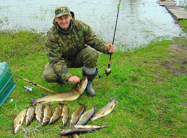Довольный рыбак в камуфляже не плохим уловом