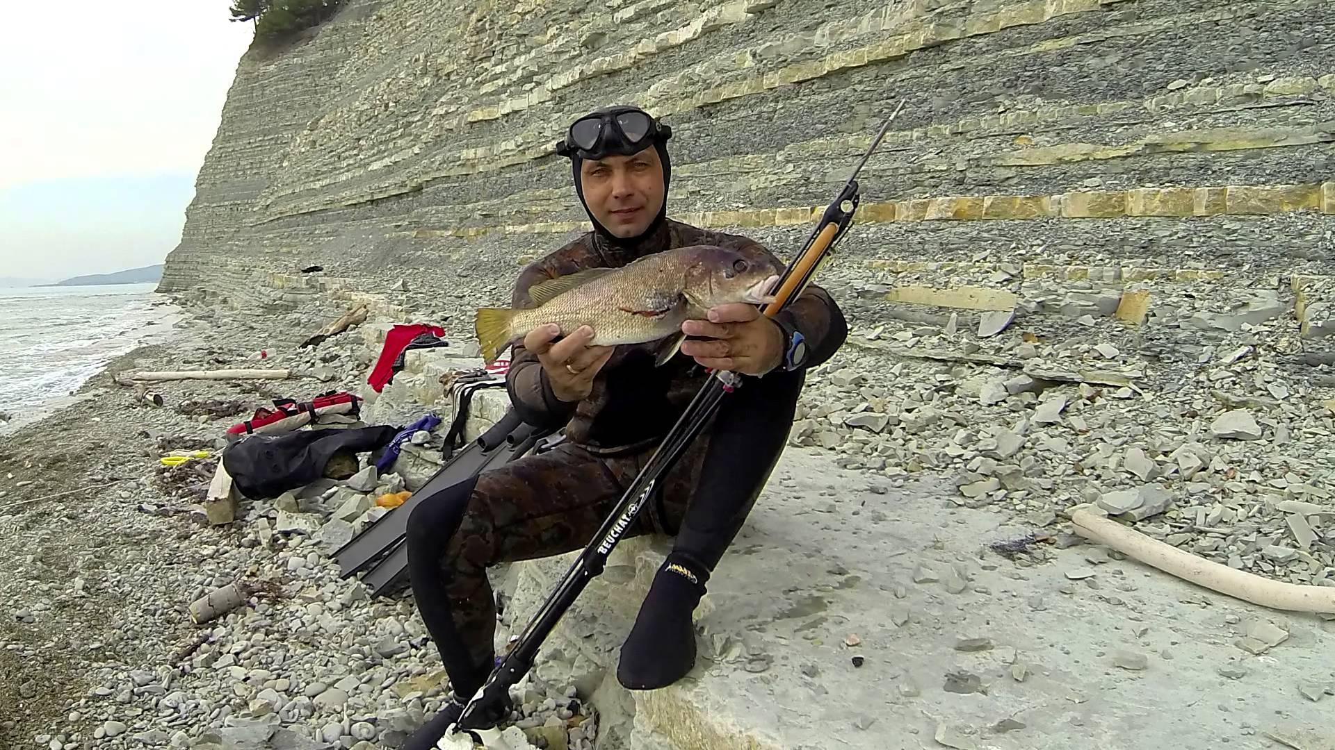 Парень в гидро костюме с рыбой в руках