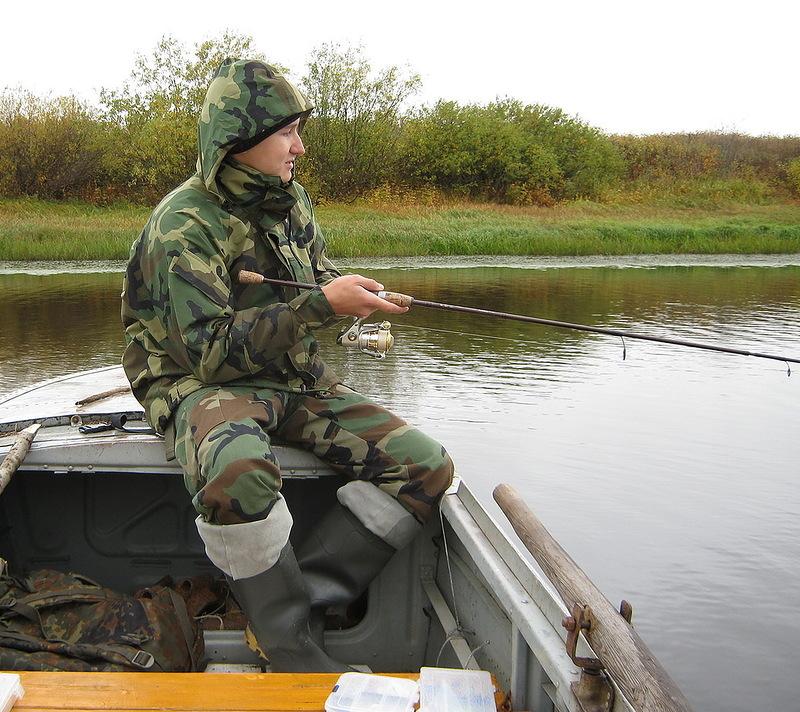 Рыбак в лодке с удочкой