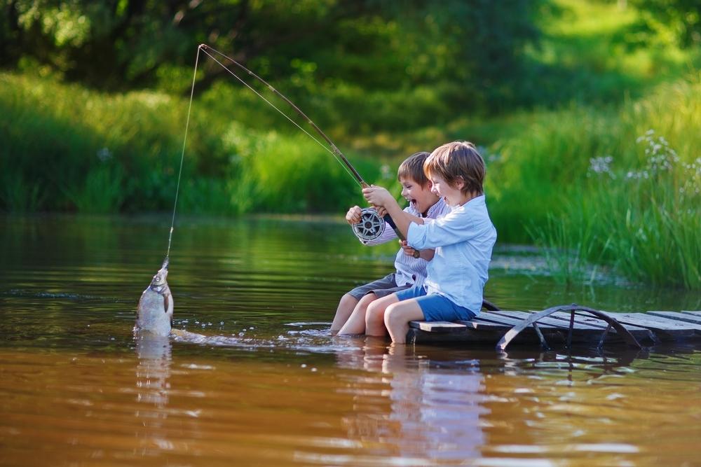 Два юных рыбака тянут рыбу