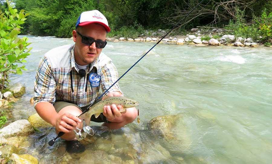 Рыбак на берегу реки с форелью