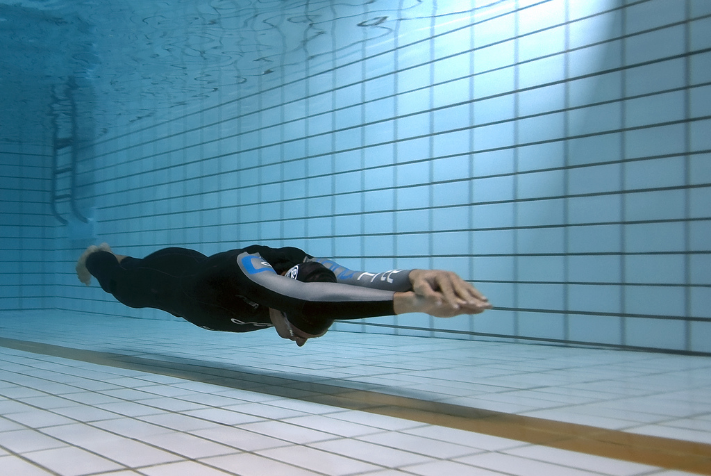 Парень в гидро костюме в бассейне