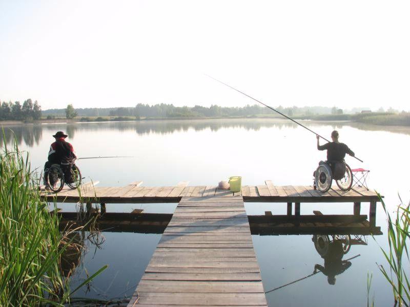 Два рыбака в креслах каталках на пристани