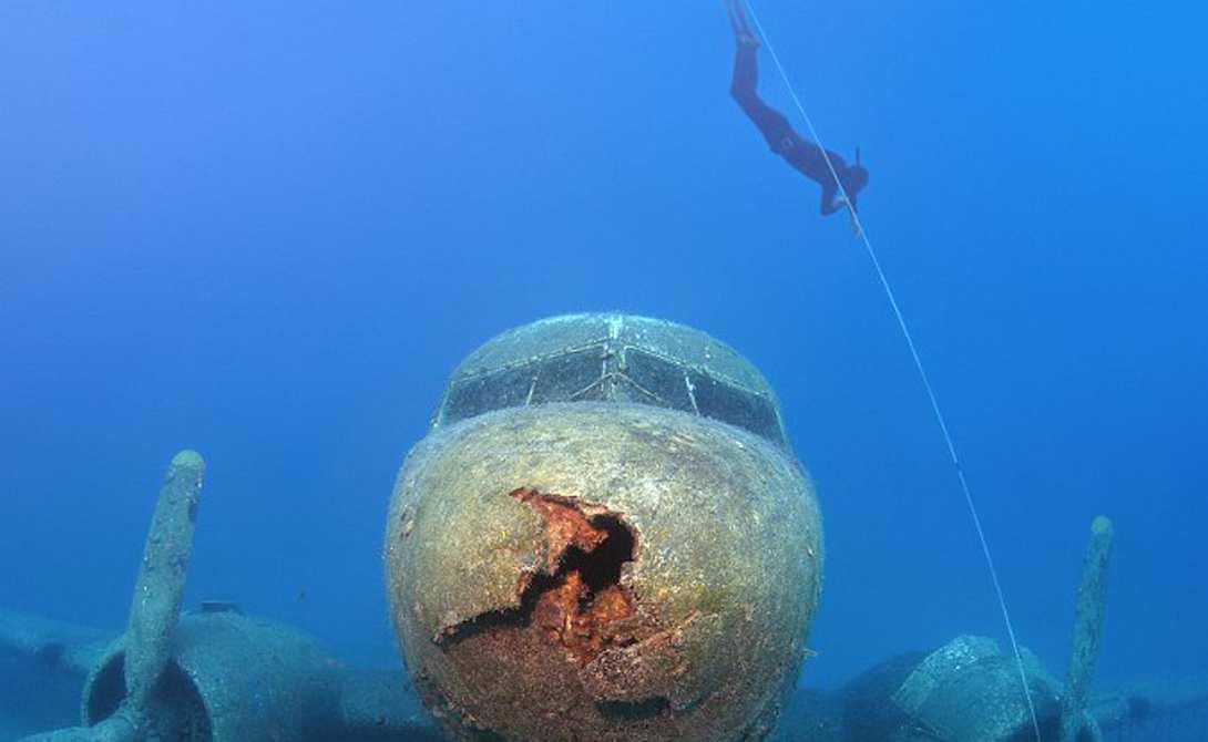 Дайвер на фоне затонувшего самолёта