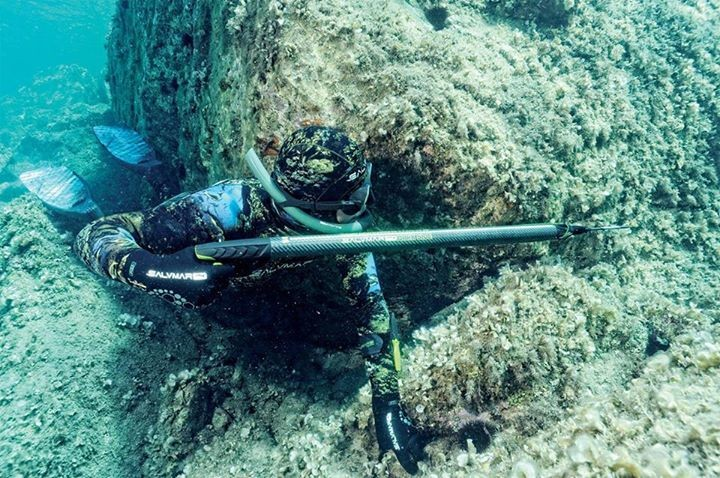 Охотник под водой в камуфлированном костюме