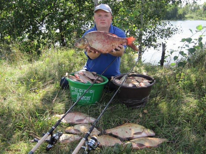 Рыбак с двумя тазиками полными рыбы