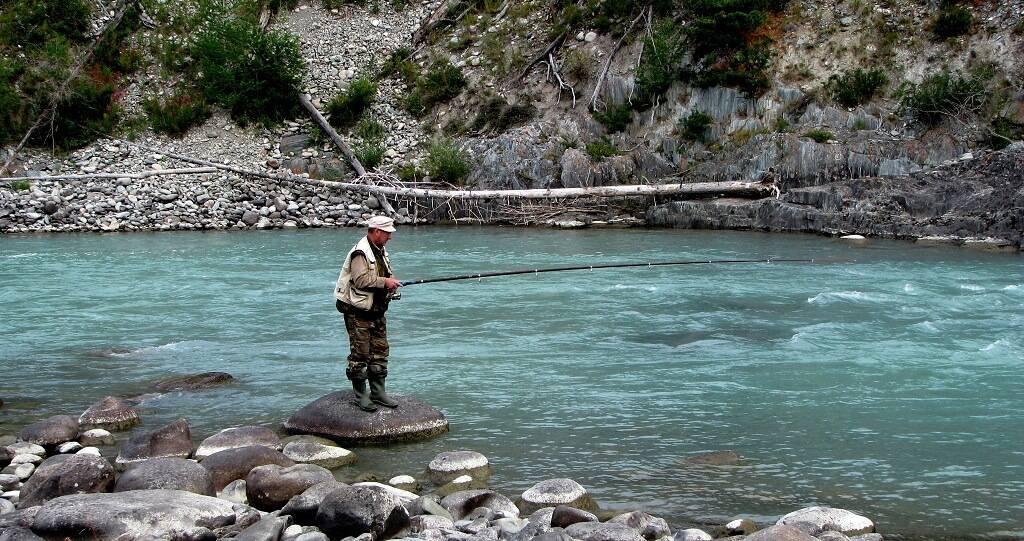 Рыбак с удочкой на реке