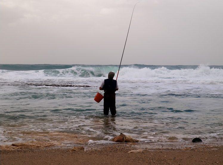 Одинокий рыбак с удочкой и ведром