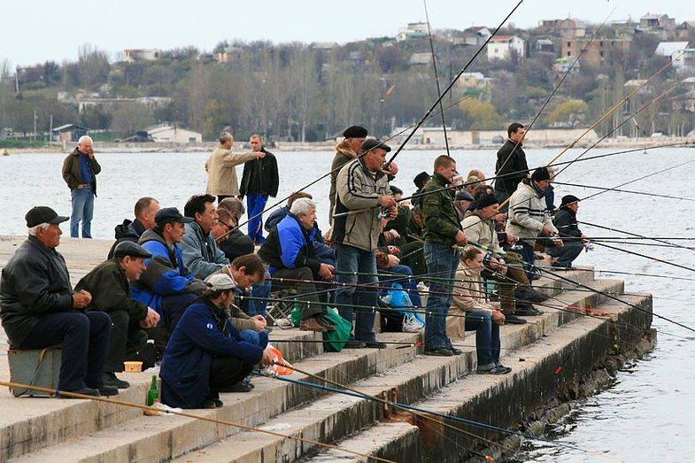 Толпа рыбаков с удочками на пирсе