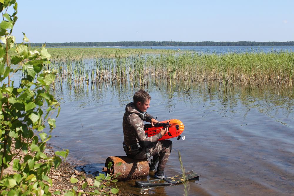 Рыбак готовит снаряжение для погружения в реку
