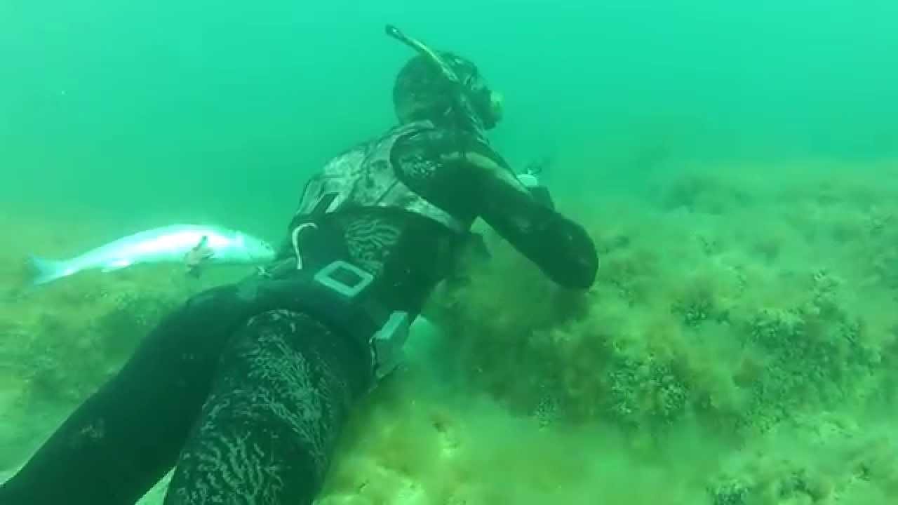 Подводный охотник в море в засаде