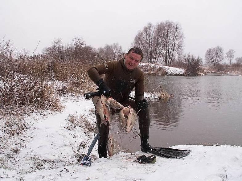 Рыбак с рыбой на берегу реки