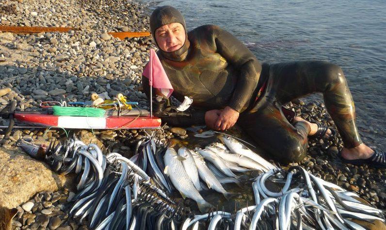Охотник с огромным уловом на берегу море