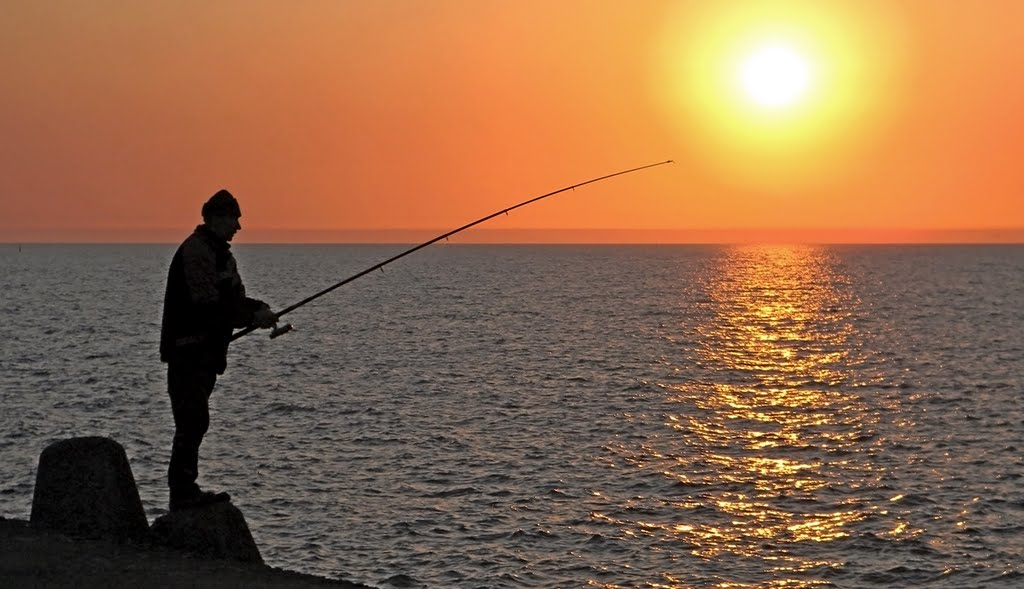 Рыбак на фоне морского заката