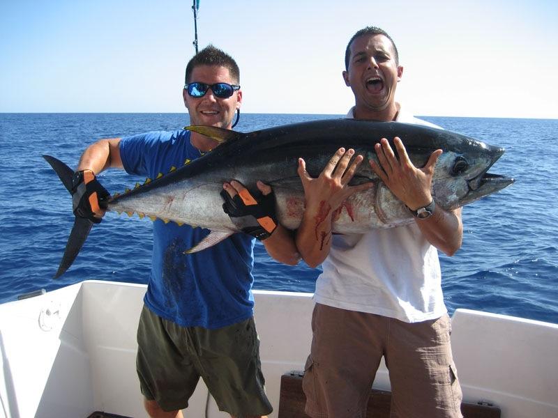 Два довольных рыбака с огромным тунцом