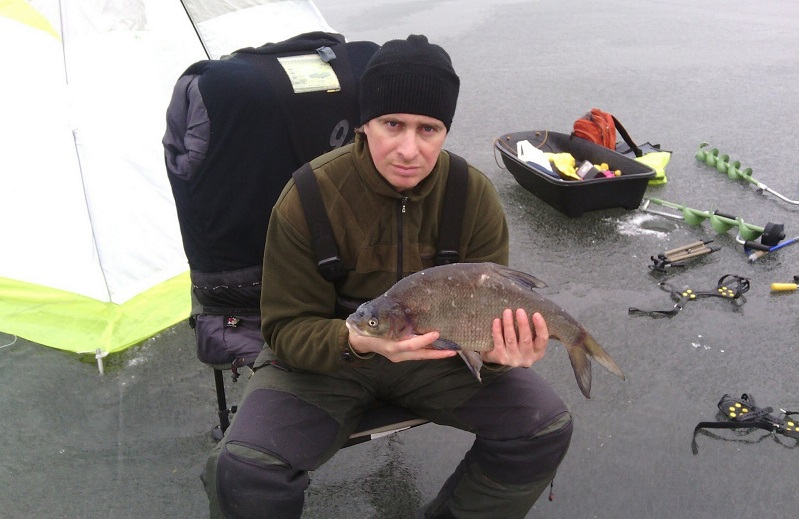 Рыбак на стуле с рыбиной