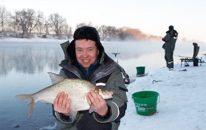 Довольный рыбак с рыбой в руках