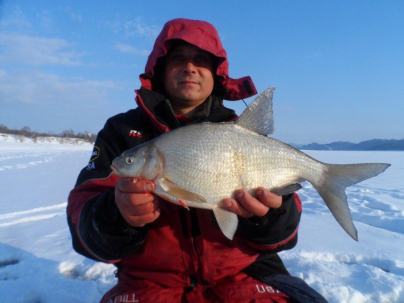 Мужик в зимнем костюме с рыбой в рукам на льду