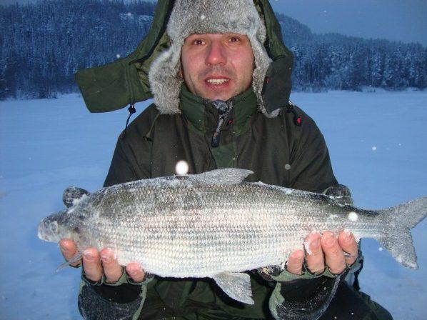 Рыбак с рыбиной в руках