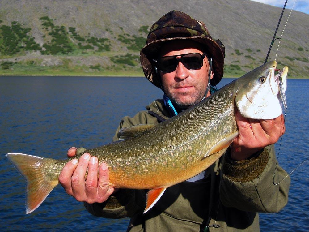 Мужик в очках с пойманной рыбой в руках