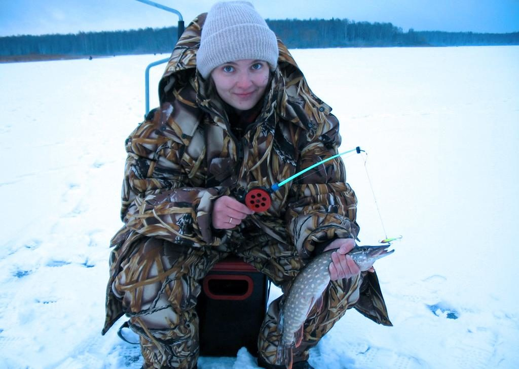 Девушка рыбачка с удочкой и рыбой в руках
