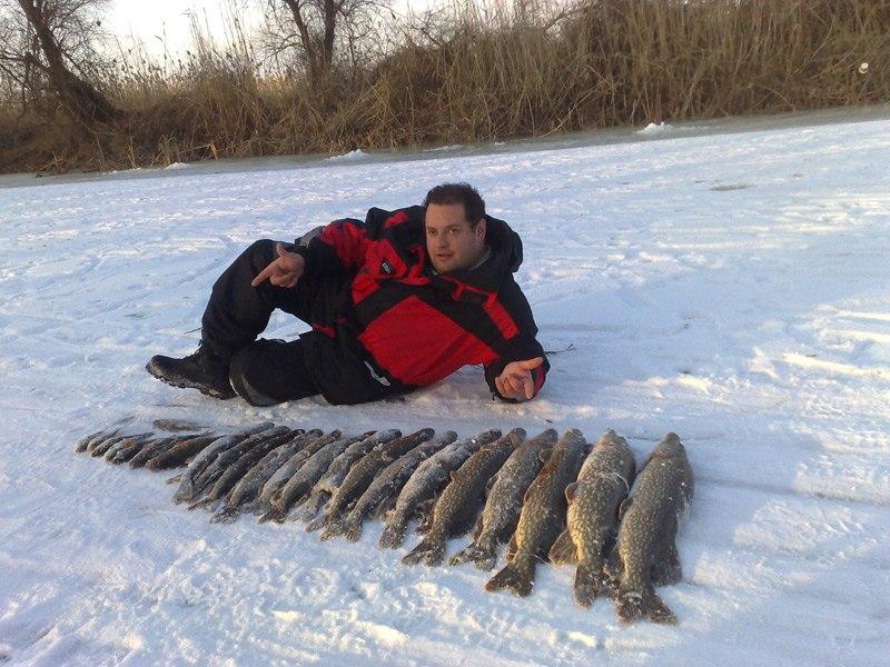 Рыбак лежа на льду