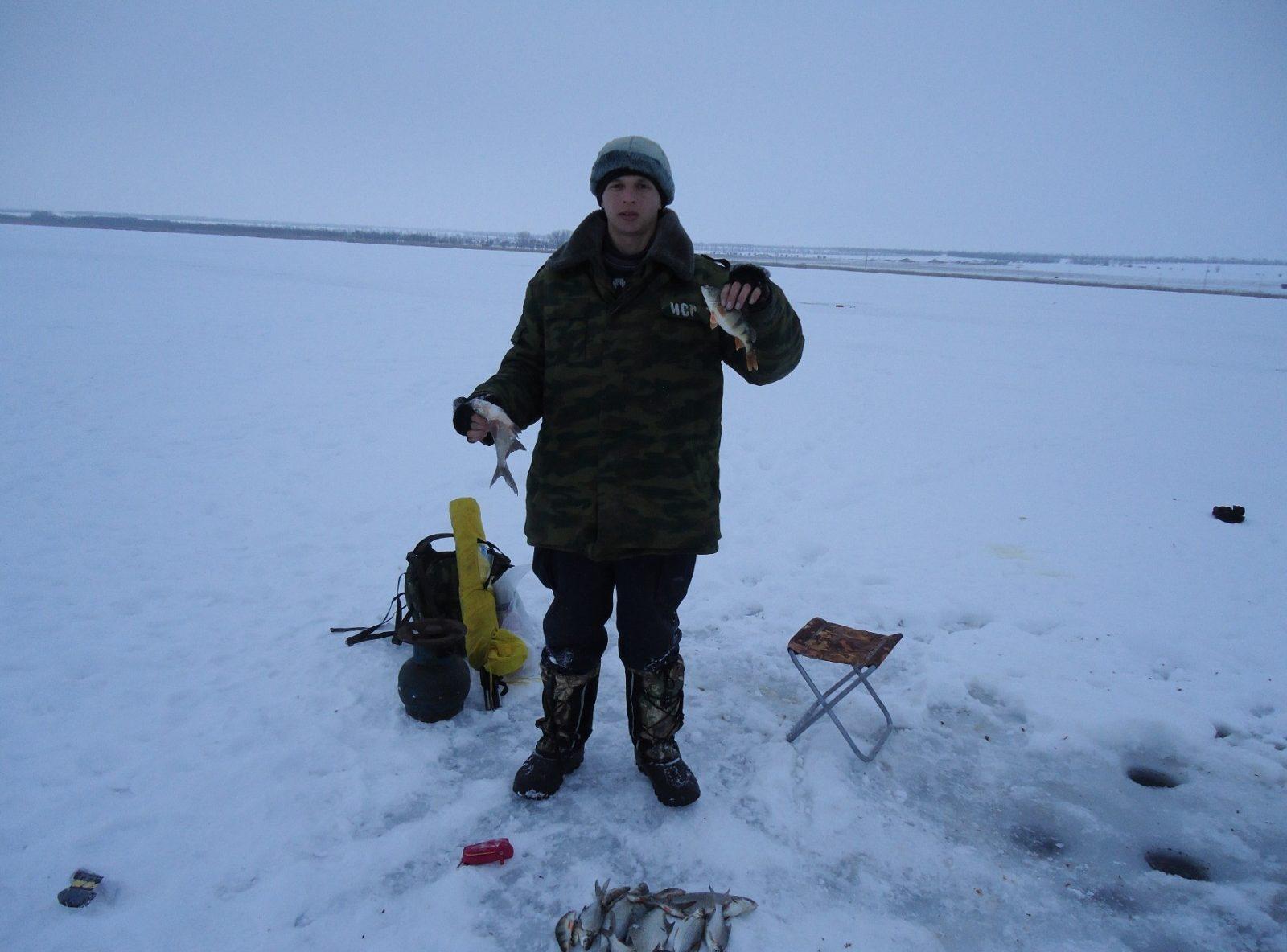 Парень на льду на зимней рыбалке