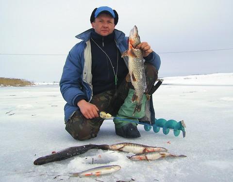 Мужик на льду с пойманной рыбой