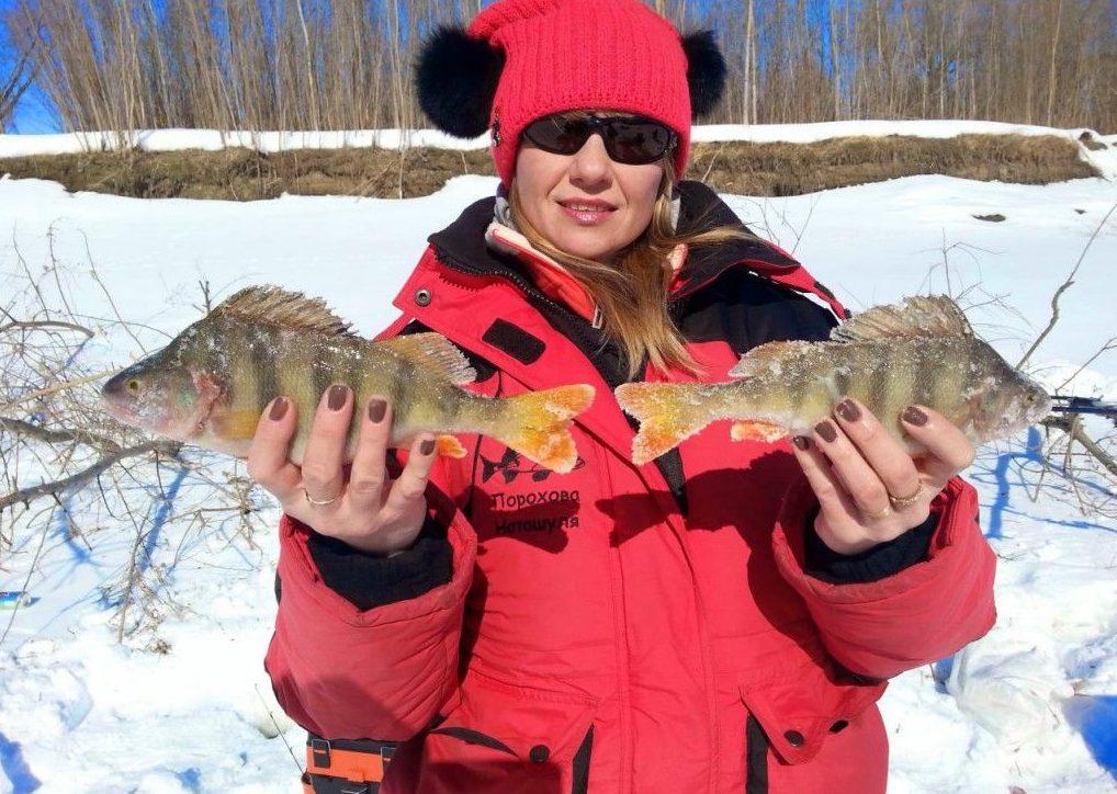Женщина рыбак с двумя окунями