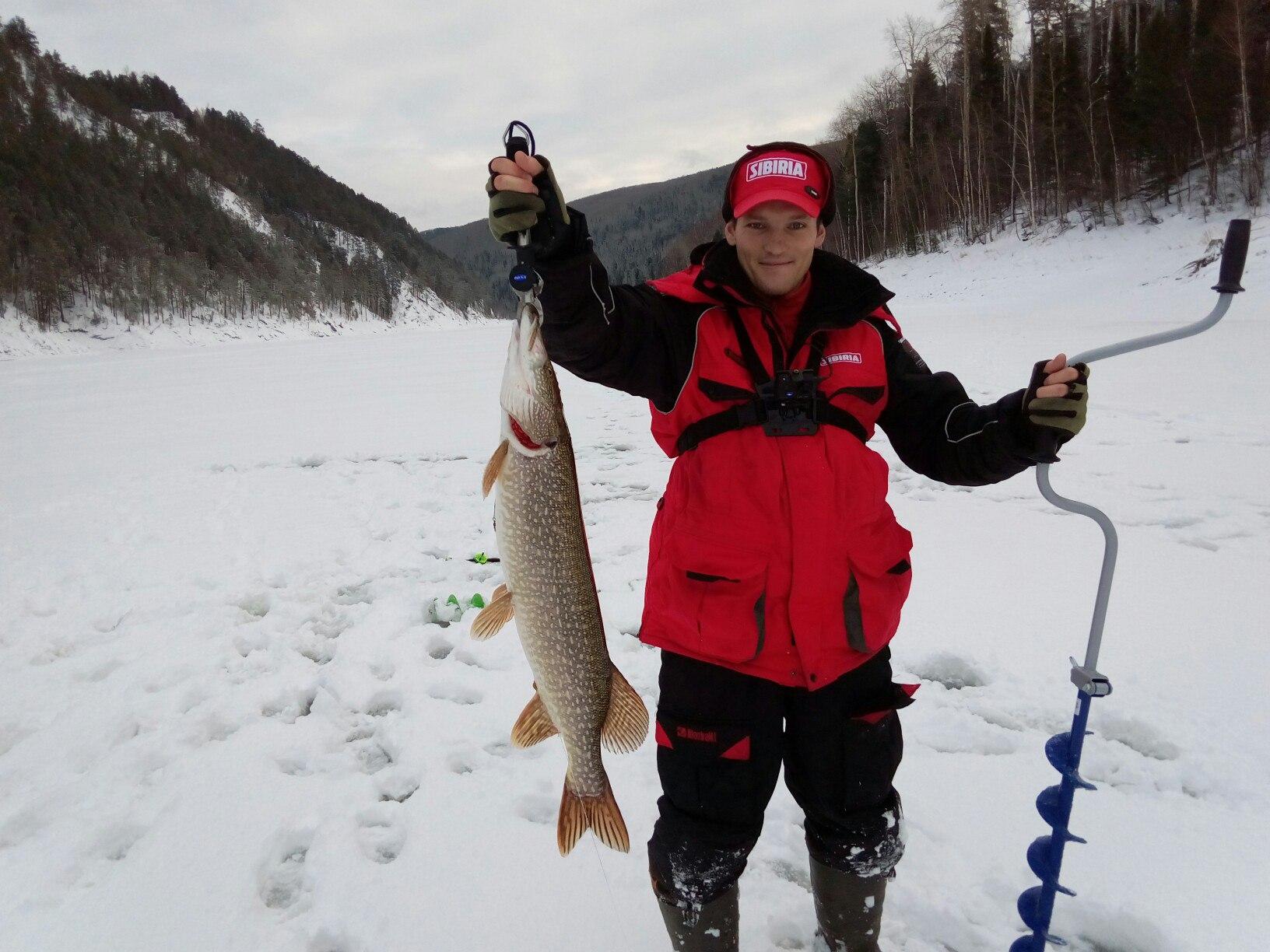 Рыбак с бурам и рыбой в руках