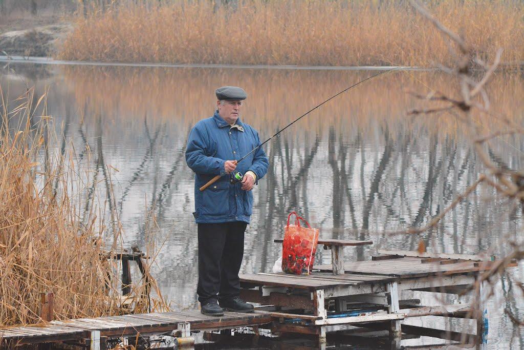 Пожилой рыбак с спиннингом