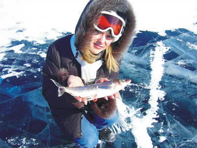 Девушка с пойманной рыбой в руках